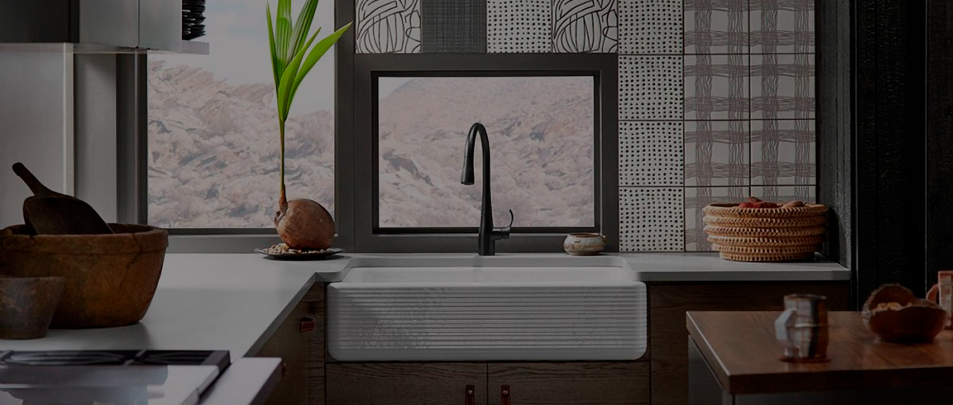 white kitchen sink with window surrounded by patterned tile