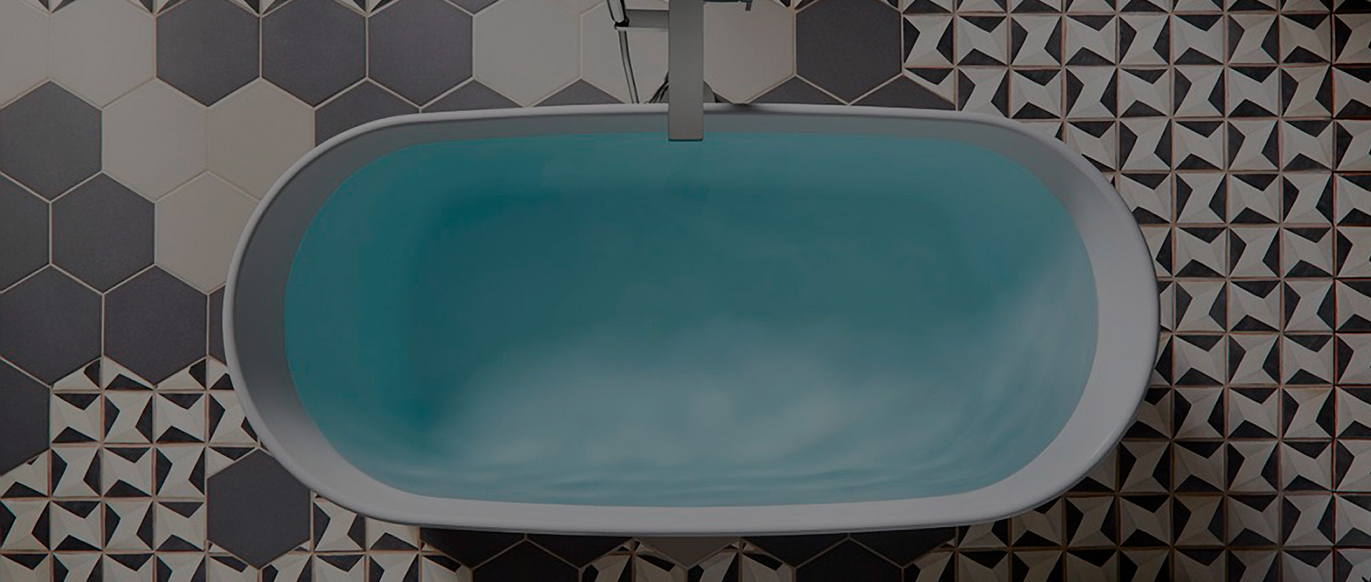 top down view of tub filled with water on top of white and gray patterned tile