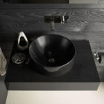 black marble sink with black wood backing